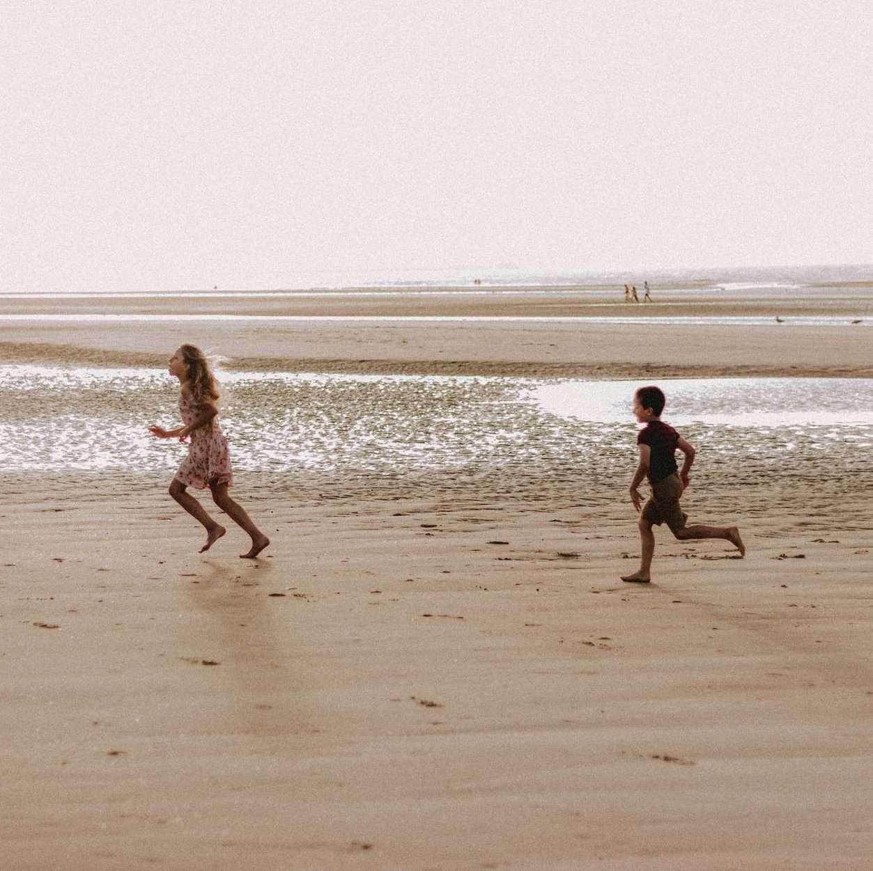 kids running on sandy beach